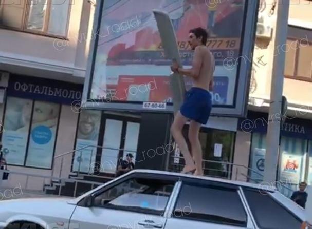 Неадекватный мужчина с крылом залез на крышу авто в Новороссийске